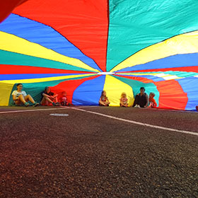 Kids playing under a parachute