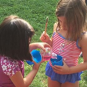 Two girls playing with bubbles