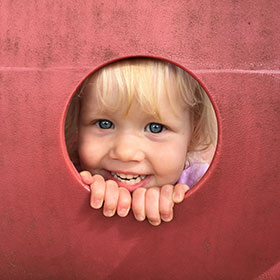 Child peering through a hole