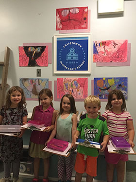 Group of children standing in front of art projects